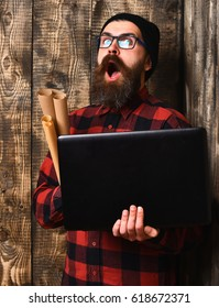 Bearded man, long beard. Brutal caucasian surprised unshaven hipster holding laptop and craft paper rolls in red black checkered shirt with hat and glasses on brown vintage wooden studio background