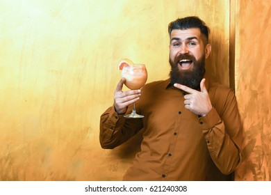 Bearded man, long beard. Brutal caucasian smiling happy hipster with moustache in brown shirt holding tropical alcoholic fresh cocktail with orange piece on golden texture background, copy space