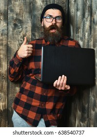 Bearded man, long beard. Brutal caucasian surprised unshaven hipster holding laptop in red black checkered shirt with hat and glasses on brown vintage wooden studio background