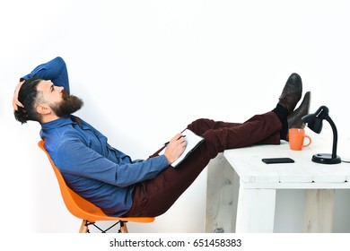 Bearded man, long beard. Brutal caucasian unshaven serious hipster with moustache writing to notepad, sitting at white vintage wooden table with black lamp on it, isolated on white background