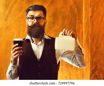 Bearded man, long beard. Brutal caucasian unshaven serious hipster with glasses and moustache holding black plastic coffee cup or mug and meal box on brown studio background