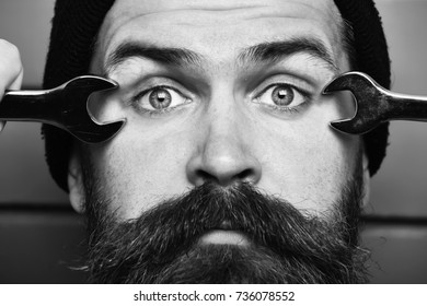 Bearded man, long beard. Brutal caucasian mechanic, unshaven hipster in black hat holding metallic wrenches on brick wall studio background. People on work concept, close up