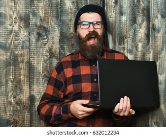 Bearded man, long beard. Caucasian unshaven hipster holding laptop in red black checkered shirt with hat and glasses on brown vintage wooden studio background