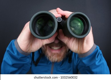 bearded man looking through binoculars on grey background