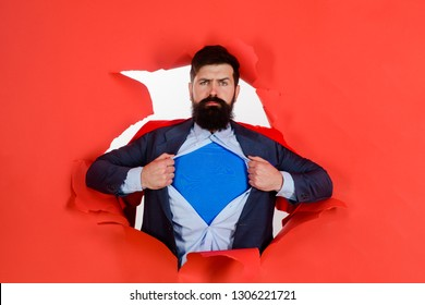 Bearded man looking through paper. Through paper. Super businessmen in red cape showing blue shirt. Save the world. Superhero. Red Superman Cape. Safety hero. Symbol S. Business growth. Super power.