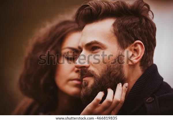 Der Bärenmann sieht weit weg, während eine schöne Brunette sein Gesicht streichelt
