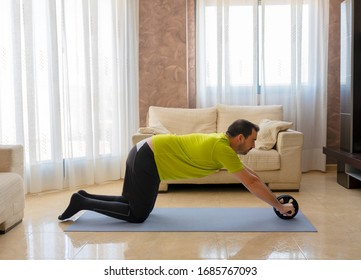Bearded man in low shape exercising with black and green sportswear in his living room in front of the sofas on a mat