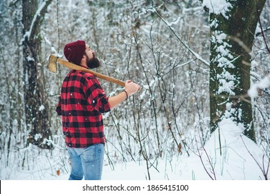 Bearded man. Lumberjack in winter snowy forest. Bearded hipster with axe. Serious lumberjack on winter day outdoors. Lumberjack lifestyle. Handsome man working in forest.