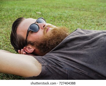 Bearded Man Lying in Grass with Sunglasses on