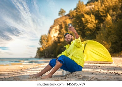 bearded man makes a selfie with a tent on a sandy beach. Active summer vacation