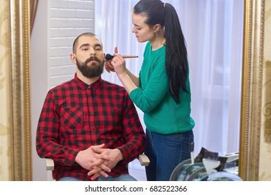 Bearded man and makeup artist. Female visagist using brush.