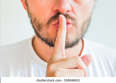Bearded man making silence gesture, pst, shh, face detail