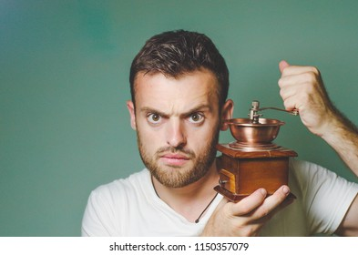 bearded man with a manual coffee grinder