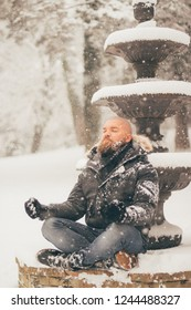 Bearded man meditates sitting on a snowy fountain while is snowing - peace of mind and healthy lifestyle concept