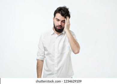 Bearded man with messy hair and beard, rubbing head and being tired or having hangover, standing over gray background. Confused and sleepy guy .