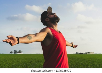 Bearded man model wearing black cap, sunglasses and red tshirt looks away, enjoing sunset in the green rice fields scenery. Blue cloud sky on background
