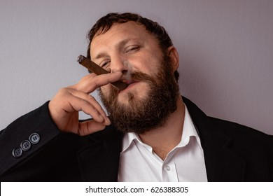 Bearded man in modern coat and shirt smoking his cigar.