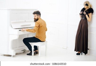 Bearded man in mustard yellow shirt playing piano while pretty girl in twenties dress and fur collar leaning on wall isolated on white background.