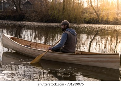 Bearded man in the nature, sitting in canoe and paddling.