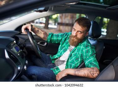 A bearded man in a new car.
