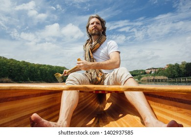 Bearded man on a boat ride. Canoeist paddling the canoe. Man rowing the wooden boat. Gondolier paddling the boat on lake