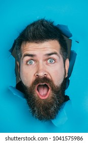 Bearded man peeking from ripped paper hole. Surprised or shocked man with beard and mustache looking through hole in blue paper. Man gazing surprisingly from hole in wall. Male head ripped blue paper.