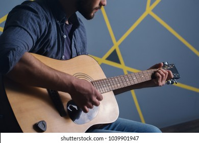 Bearded man playing the guitar, close-up