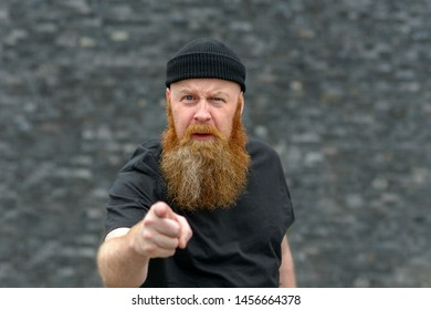 Bearded man pointing at the camera in disbelief frowning in puzzlement with focus to his face over grey