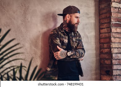 Bearded man posing over the wall in a room with loft interior.