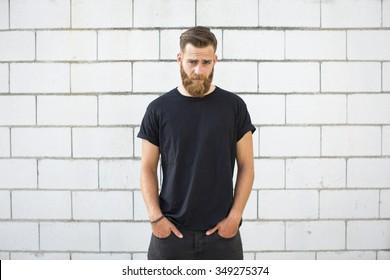Der bärtige Mann posiert auf der Straße.