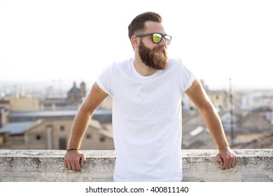Bearded man posing in the street with sunglasses.