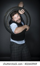 Bearded man posing in studio with old motorcycle tyre