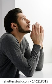 Bearded man praying. Portrait of bearded man praying to god and holding his hands clasped