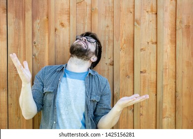 A bearded man raises his palms and head up and makes a moan. Emotions of despair and problems. Isolated on the background of an old wooden wall. Close-up.