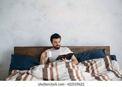 Bearded man reading a big book lying in his bedroom under the blanket. Nice guy holding paperback in left hand and tea cup in right hand. He has wonderful morning today