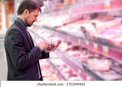 A bearded man reads information about the product, stands near the refrigerator in the supermarket in the meat department