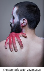 Bearded man with red painted hands embracing himself. Profile from the back, face painted in tribal makeup. Head and shoulders.