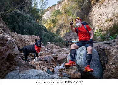 Bearded man in red shirt with dog near the river in the forest. Outdoor travel concept