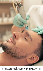 Bearded man relaxing with closed eyes while a professional cosmetologist nourishing the skin of his forehead