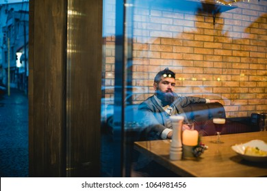 Bearded man rest in restaurant with beer glass. Beer time. serious bar customer sit in cafe drinking ale. Date meeting of hipster awaiting in pub. Businessman with long beard drink in cigar club.
