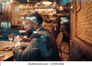 Bearded man rest in restaurant with beer glass. Businessman with long beard drink in cigar club. Beer time. serious bar customer sit in cafe drinking ale. Date meeting of hipster awaiting in pub