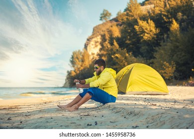 bearded man resting with a tent on a sandy beach. Active summer vacation
