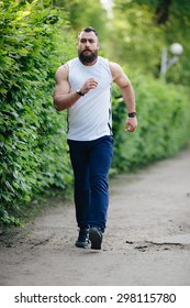 bearded man running a cross in the park at green fence
