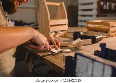 a bearded man in safety glasses and an apron works in a carpentry shop