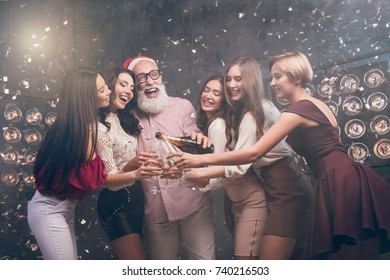 The bearded man in Santa's hat pours champagne into girl's glasses and smile. Modern Santa in Christmas hat have a fun with girls in the club with confetti. Happy New Year 2018