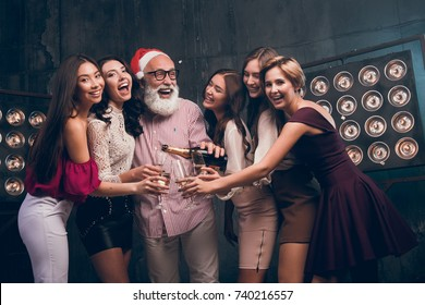 The bearded man in Santa's hat pours champagne into girl's glasses and smile. Modern Santa in Christmas hat have a fun with girls in the club. Happy New Year 2018