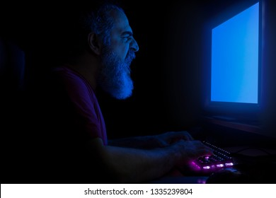 Bearded man screaming in front of computer monitor, hands on a keyboard, working, frustrated, illuminated with blue light from monitor