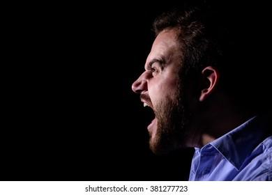 Bearded man screams into the dark