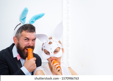 bearded man and sexy girl. copy space. Rabbits family with bunny ears. Holiday celebration, preparation. Easter bunny. happy easter. spring holiday. Egg hunt. easter bunny couple eat orange carrot.