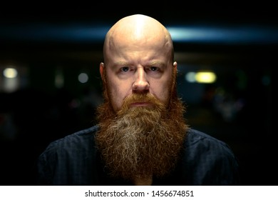 Bearded man with shaved head staring at the camera with an ill-tempered frown and cross expression lit from above at night in a close up portrait